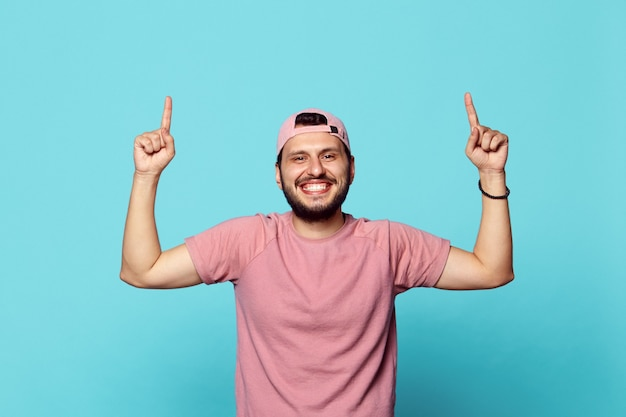 Człowiek wskazując palcami w górę na lato na białym tle nad ścianą niebieski studio