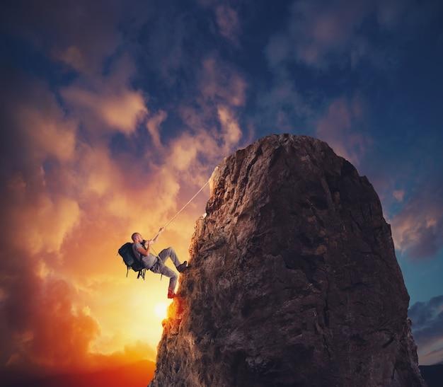 Człowiek wspina się na górę, aby zdobyć flagę. cel osiągnięcia i trudna koncepcja kariery