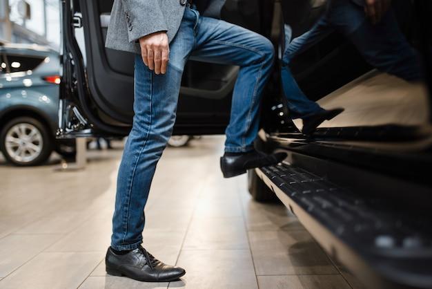 Człowiek wybierając pickupa w salonie samochodowym. klient w salonie samochodowym, mężczyzna kupujący transport, firma dealera samochodowego dealer