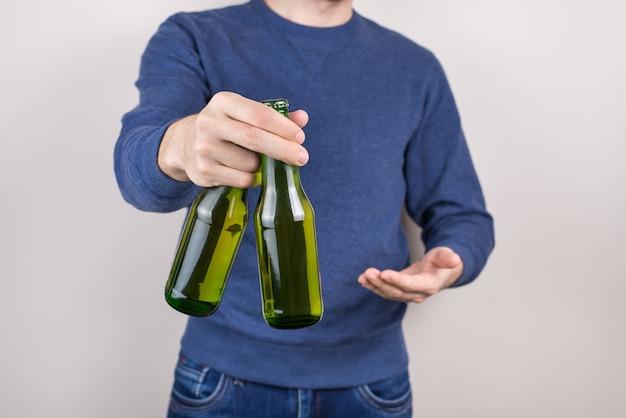 Człowiek, wykazując dwie zielone butelki szklane na białym tle szarym tle