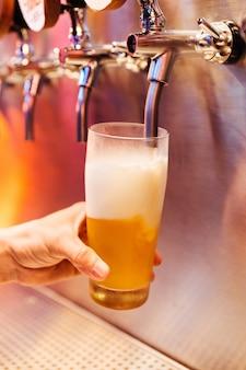 Człowiek wylewanie piwo rzemieślnicze z kranów piwa w mrożone szkło z piany.