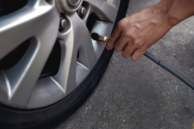 Człowiek wypełniający powietrze w oponach. kierowca samochodu sprawdzanie ciśnienia i konserwacji