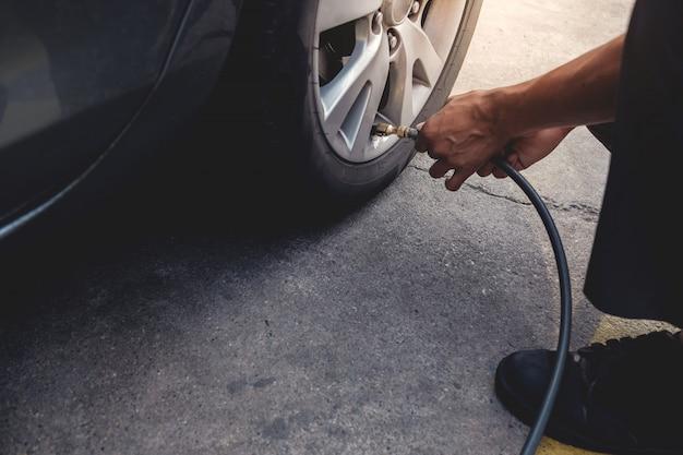 Człowiek wypełniający powietrze w oponach. kierowca samochodu sprawdzanie ciśnienia powietrza i konserwacja jego samochodu