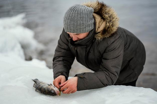Człowiek wypuszczający rybę z przynęty wędziska