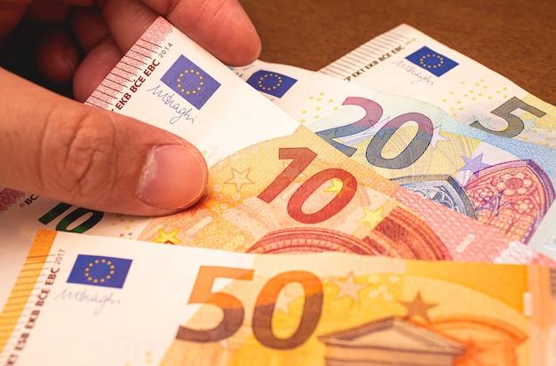 Człowiek z banknotami euro do finansowania biznesu i koncepcji zarabiania pieniędzy