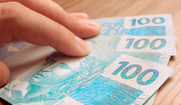 Człowiek z banknotami stu reali brazylijskiego reala, które leżą na drewnianych meblach