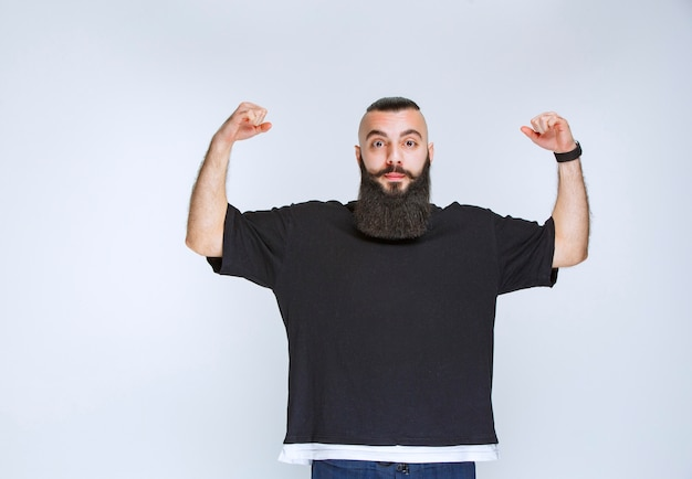 Człowiek z brodą bardzo się cieszy z czegoś.