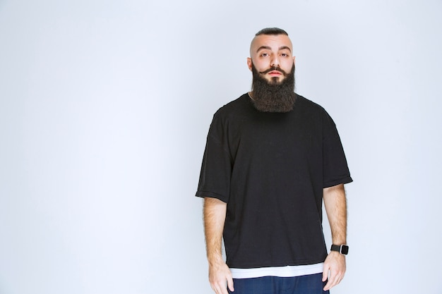 Człowiek z brodą dając atrakcyjne pozy.