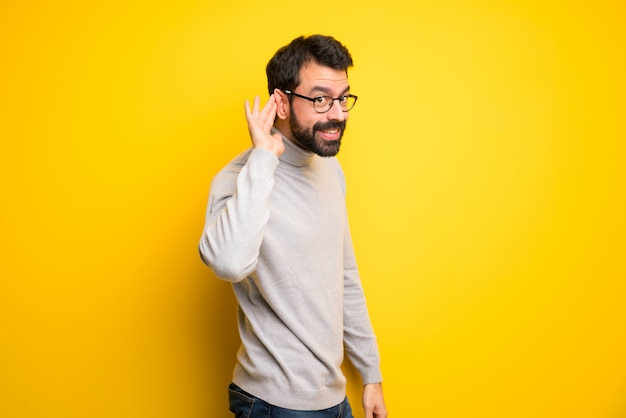 Człowiek z brodą i golfem słuchając czegoś, kładąc rękę na uchu