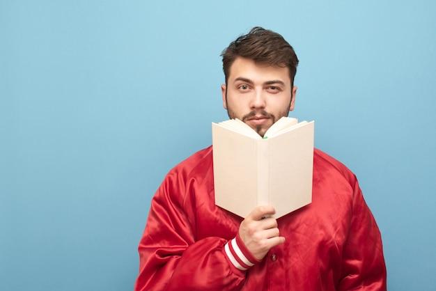 Człowiek z brodą i książką w ręku na niebiesko