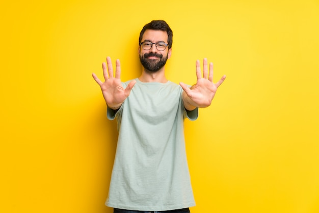 Człowiek z brodą i zieloną koszulą licząc dziesięć palcami