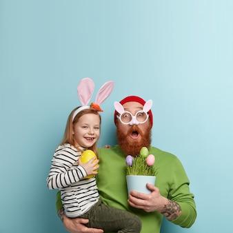 Człowiek z brodą imbir na sobie kolorowe ubrania i trzymając córkę