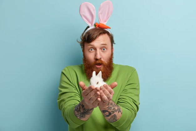 Człowiek z brodą imbir na sobie kolorowe ubrania i trzymając królika