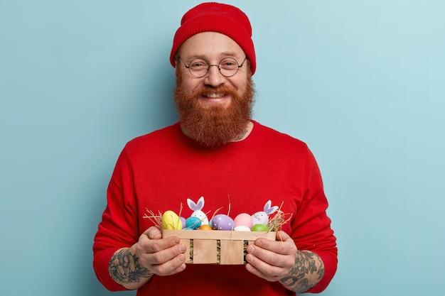 Człowiek z brodą imbir na sobie kolorowe ubrania i trzymając pisanki
