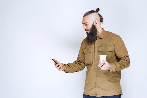 Człowiek z brodą sprawdzanie wiadomości przy kawie.