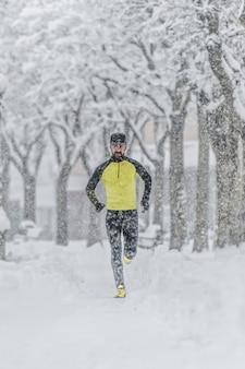 Człowiek z brodą trenuje, biegając po śniegu w mroźną zimę