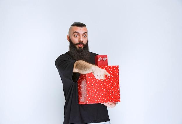 Człowiek z brodą, trzymając czerwone pudełka na prezenty i wskazując coś do przodu.