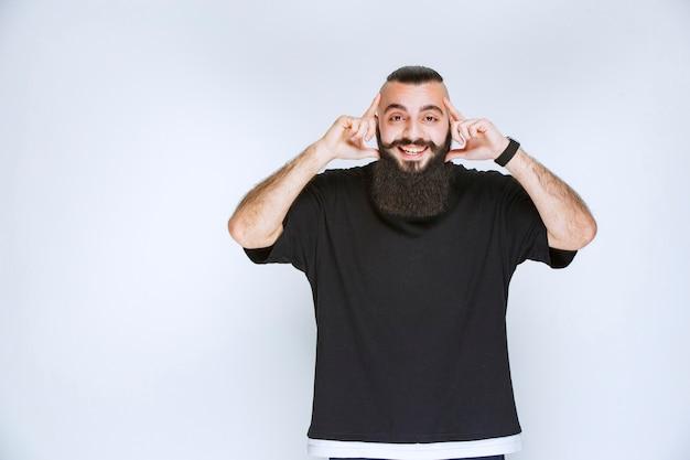 Człowiek z brodą wskazując głową, uśmiechnięty i myślący.