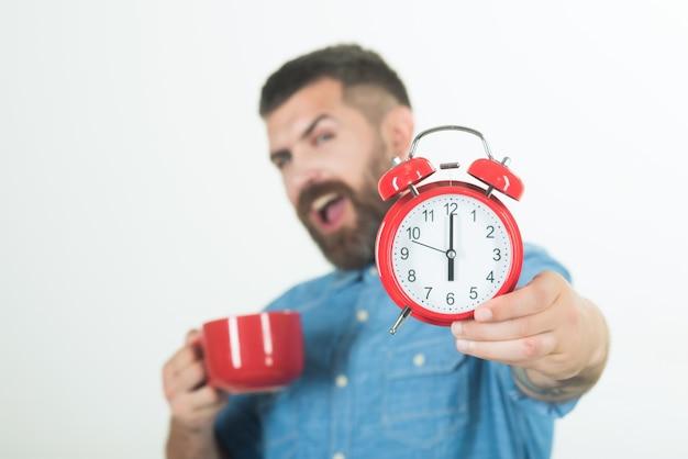 Człowiek z budzikiem, poranna przerwa na odświeżenie i hipster energii z zegarem czasu filiżanki mleka na białym człowieku pić poranną kawę lub herbatę z budzikiem