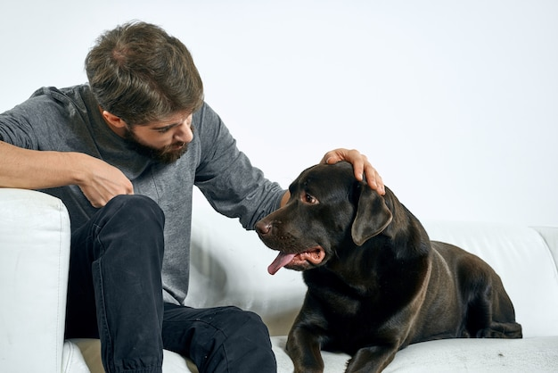 Człowiek z czarnym psem na białej kanapie na świetle