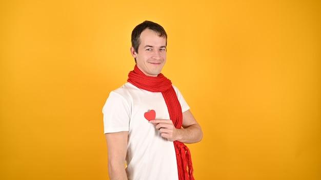 Człowiek z czerwonym sercem w rękach na żółto