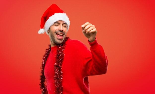 Człowiek z czerwonymi ubraniami świętuje świąt bożego narodzenia cieszyć się tańcem podczas słuchania m