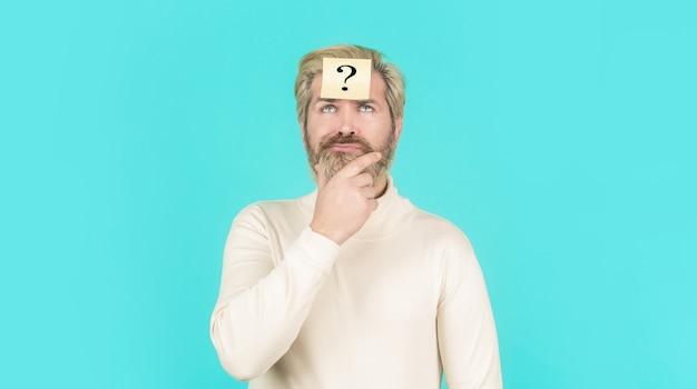 Człowiek z czołem ze znakiem zapytania, patrząc w górę. notatki papierowe