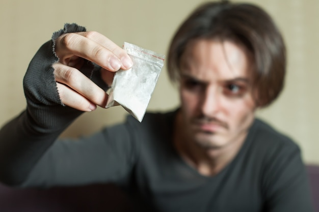 Człowiek z dawką kokainy w dłoni.