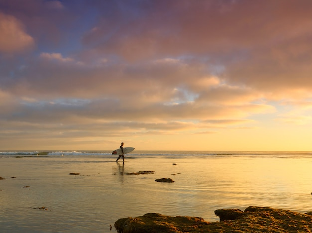 Człowiek z deską surfingową w morzu z pięknym zachodem słońca