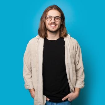 Człowiek z długimi włosami i brodą w okularach uśmiecha się do kamery na ścianie niebieskie studio
