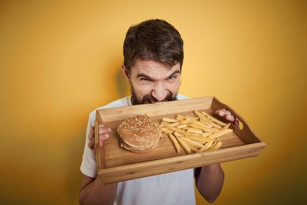 Człowiek z drewnianą paletą fast food hamburger frytki dieta spożycie żywności z bliska