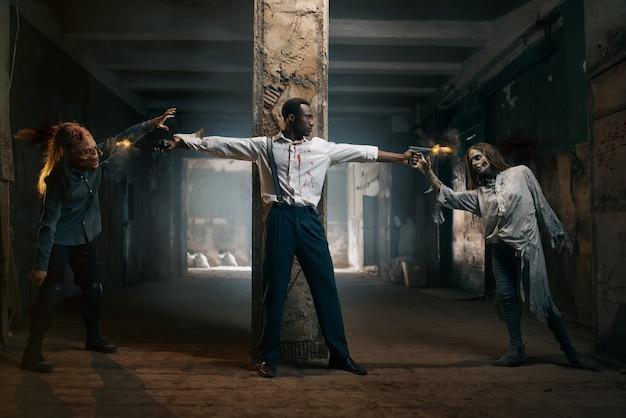 Człowiek z dwoma pistoletami strzela do zombie, śmiertelnie pościg w opuszczonej fabryce. horror w mieście, przerażający atak pełzaczy, apokalipsa końca świata, krwawe złe potwory
