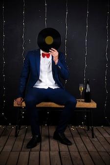 Człowiek z dysku fonografu w pobliżu butelki i szkła
