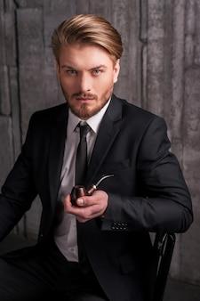 Człowiek z fajką. przystojny młody mężczyzna w stroju formalnym trzymający fajkę i patrzący w kamerę siedząc na krześle