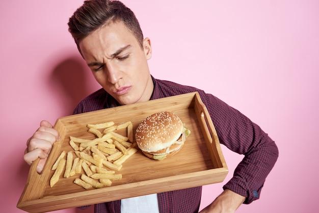 Człowiek z fast foody jedzenie hamburgerów frytki na różowym tle.