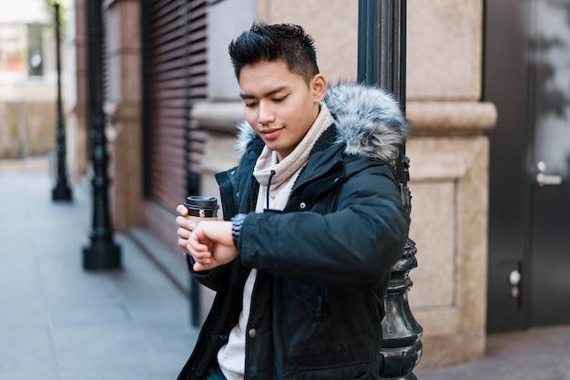 Człowiek z filiżanką kawy patrząc na zegarek