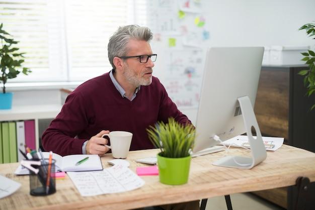 Człowiek z filiżanką kawy pracuje na komputerze