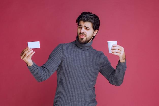 Człowiek z filiżanką kawy przedstawiający rachunek lub wizytówkę.
