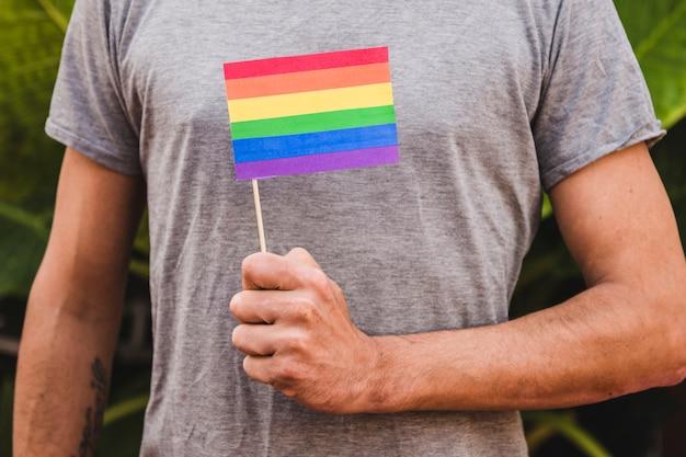 Człowiek z flagą w kolorach lgbt w ręku