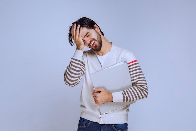 Człowiek z folderu, trzymając głowę i uśmiechając się.