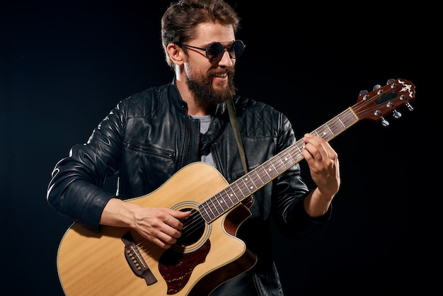 Człowiek z gitarą w dłoniach czarna skórzana kurtka okulary przeciwsłoneczne muzyka emocje czarne tło