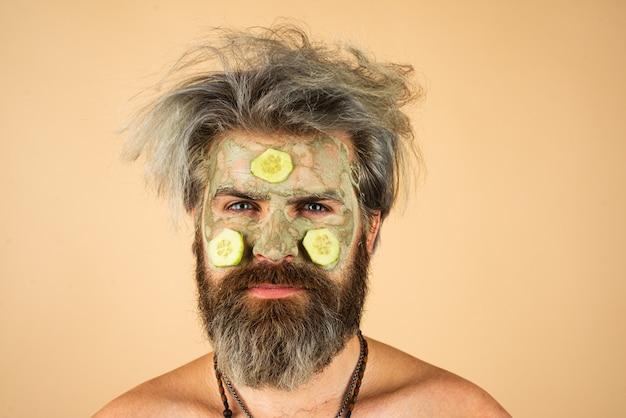 Człowiek z glinianą maską i plasterkami ogórka na twarzy spa dermatologia wellness i koncepcja leczenia twarzy...