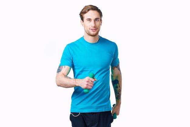 Człowiek z hantlami w ręce treningu fitness ćwiczenia światło tło. zdjęcie wysokiej jakości