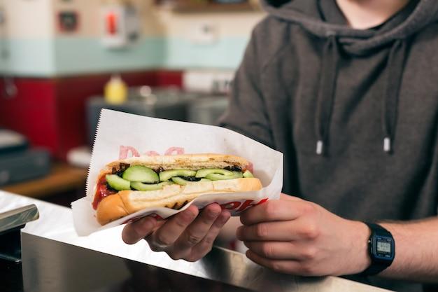 Człowiek z hot-dog w barze przekąskowym fast food