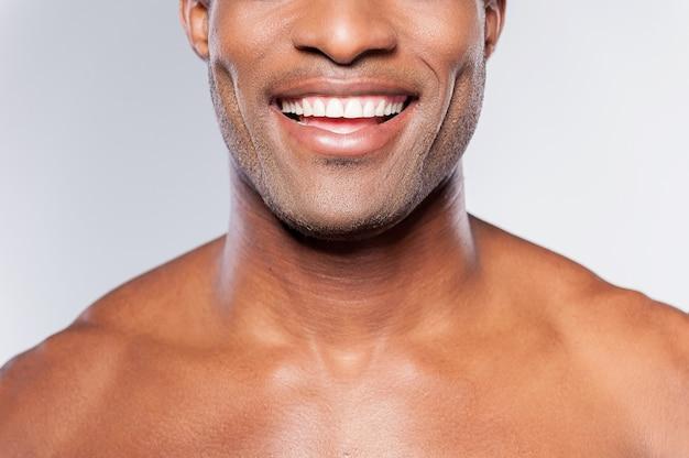 Człowiek z idealnym uśmiechem. przycięty obraz młodego afrykańskiego mężczyzny bez koszuli uśmiechającego się stojąc na szarym tle