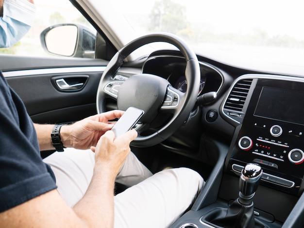 Człowiek z inteligentny telefon w samochodzie