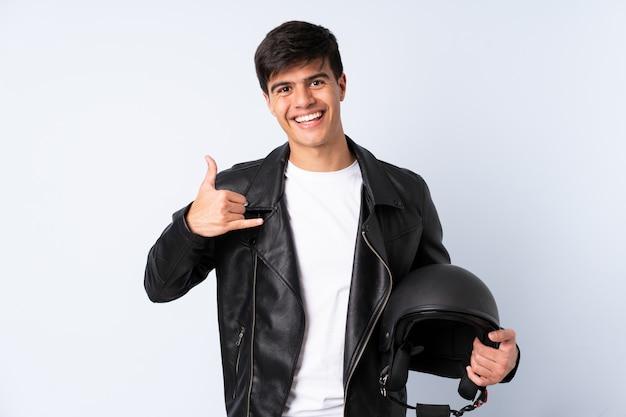 Człowiek z kaskiem motocykla na niebieską ścianą co gest telefonu