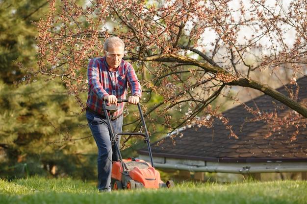 Człowiek z kosiarki elektrycznej, koszenia trawnika. ogrodnik przycinanie ogrodu. słoneczny dzień, przedmieście, wieś. dorosły mężczyzna przycinanie i kształtowanie ogrodu, przycinanie trawy, trawnika, ścieżek. ciężka praca nad naturą.