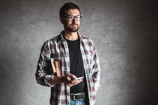 Człowiek z książkami i patrząc na ekran smartfona. pojęcie edukacji