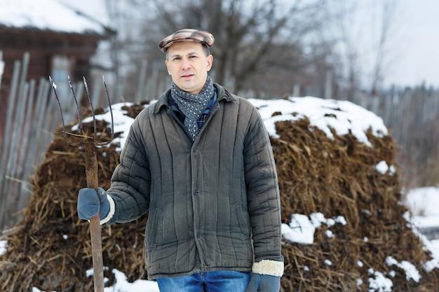 Człowiek z kupą widelca obornika wczesną wiosną